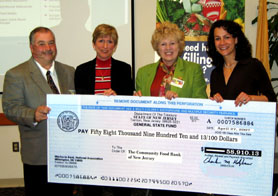 Photo of Ed Cier, Emma Davis-Kovacs and Human Services Commissioner Jennifer Velez presenting Kathleen DiChiara of Community FoodBank of NJ with Grant Check - Click to enlarge