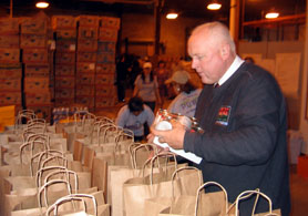Photo of Secretary Kuperus filling grocery bags - Click to enlarge