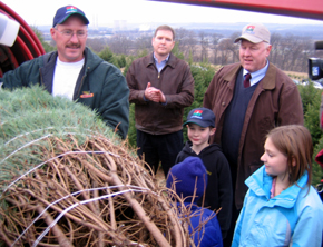 Photo of John Wyckoff baling the tree as Assemblyman Doherty and Secretary Kuperus look on