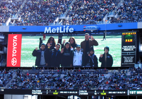 Photo of school reps on the field at the NY Jets game - Click to enlarge