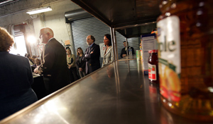 Photo of Governor Corzine and Secretary Kuperus in front of empty shelves at CUMAC