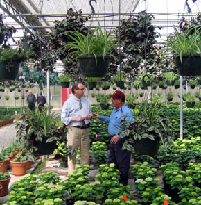 Photo of Secretary Fisher and Carmen La Rosa in the greenhouse