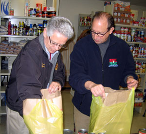 Photo of Assemblyman Jack Conners and Secretary Fisher packing groceries