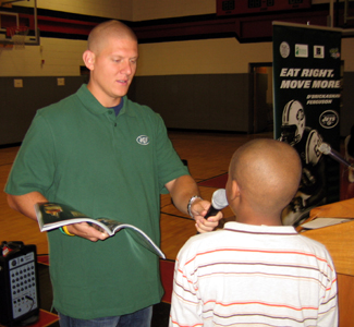 Photo of Jets Kicker Nick Folk handing out a prize during the program
