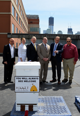 Photo of officials on the roof of the Hyatt Regency Jersey City with a new resident beehive.