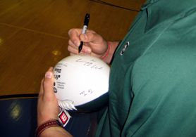 Photo of NY Jets Kenwin Cummings signing a football - Click to enlarge