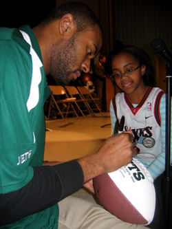 Photo of NY Jets Marques Murrell signing a football for a student