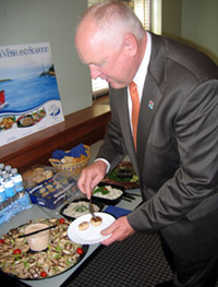 Photo of Secretary Kuperus inspecting Jersey Seafood dishes at Seafood Challenge Kickoff
