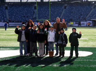 Photo of school representatives on the field at the Jets game.