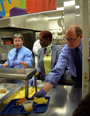 Photo of Jim Harmon, Cherrie Walker and Secretary Fisher serving lunch.