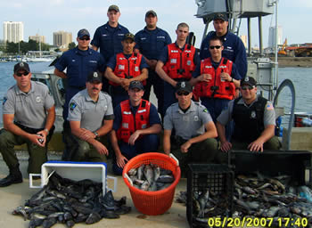 Officers with seized fish
