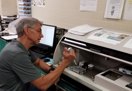 photo: July 23, 2019 HarmfulResearch Scientist at the DEP's Bureau of Freshwater and Biological Monitoring performs toxin analysis using a Cyanotoxin Automated Assay System. Source: DEP.