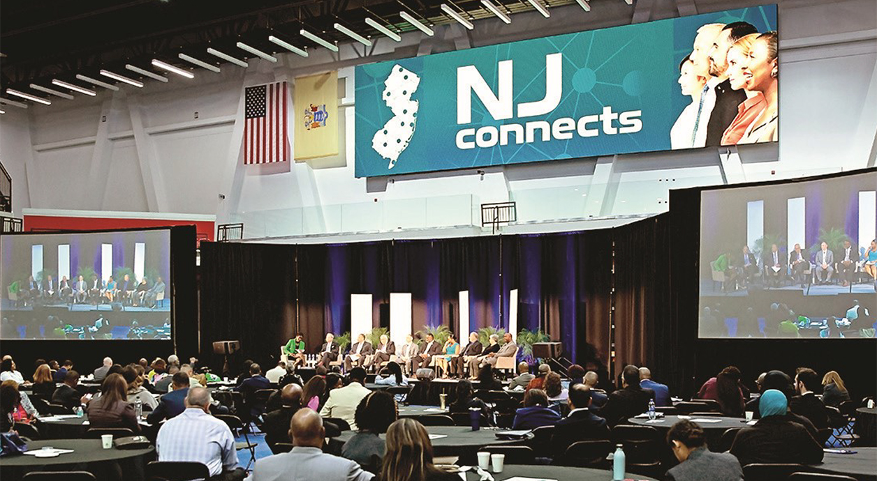 NJ connects banner above a stage in a large room full of people