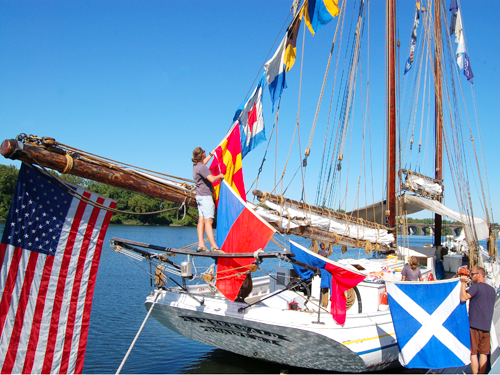 The crew of the A.J. Meerwald, NJ's Official Tall Ship, hoists colorful pennants into the rigging while docked at Trenton
