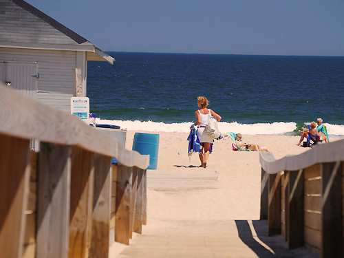A woman looks for a good spot to relax as she enters the beach at Ocean Grove