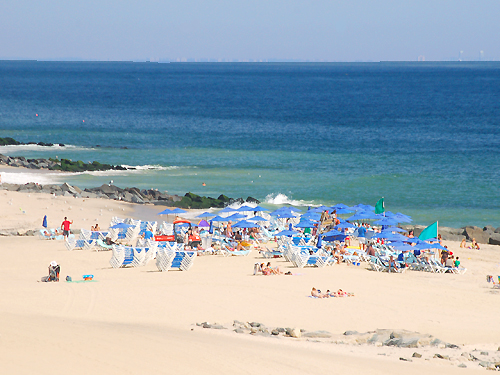 A cluster of blue umbrellas line the beach at Long Branch