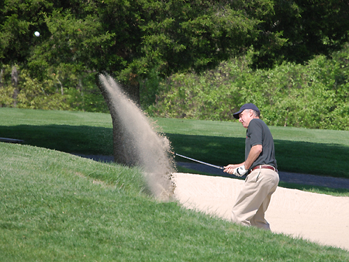 A golfer sprays sand as he swings his way out of a bunker at the Spring Meadow Golf Course near Farmingdale