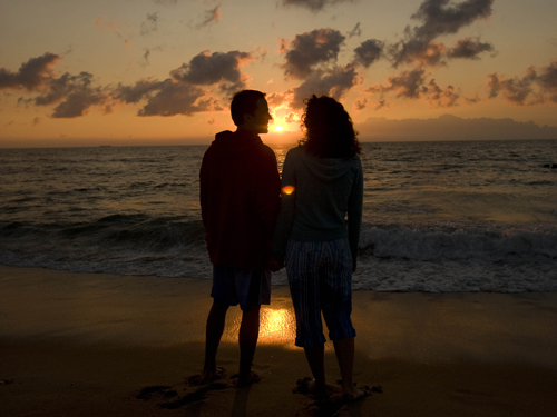 Couple enjoying a glorious sunrise at the Jersey shore